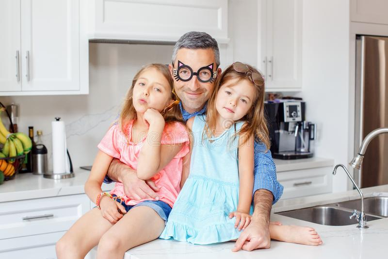 Papa caucasien de père portant les lunettes drôles étreignant embrassant deux filles d'enfants photos stock
