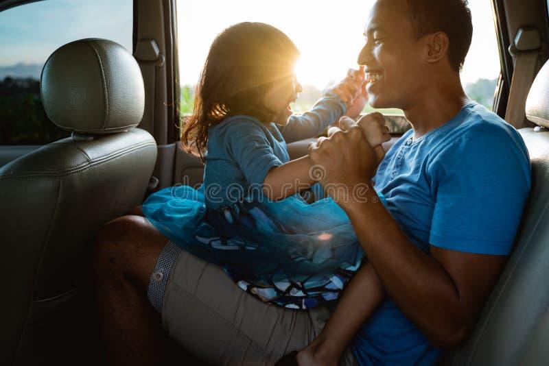 Papa chatouillant sa petite fille dans la voiture photographie stock libre de droits