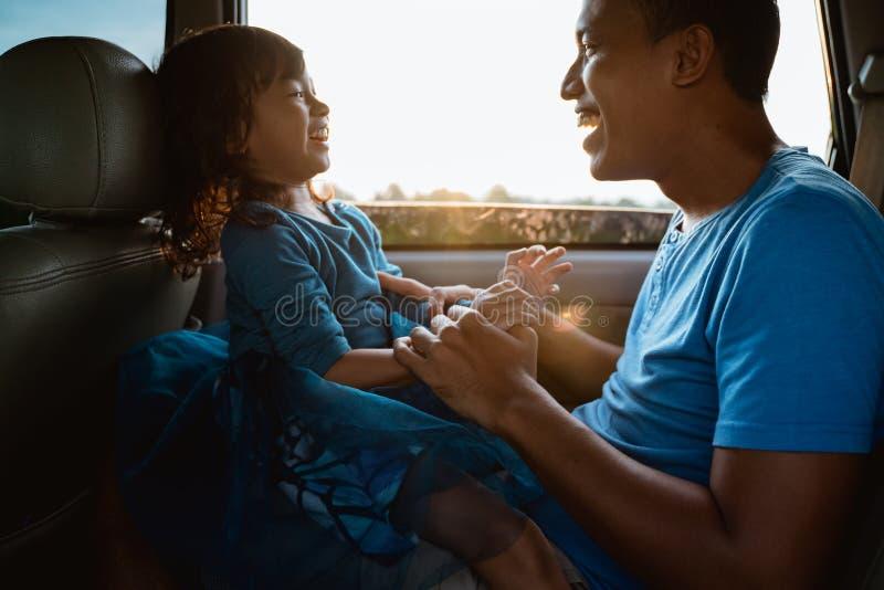 Papa chatouillant sa petite fille dans la voiture photos libres de droits