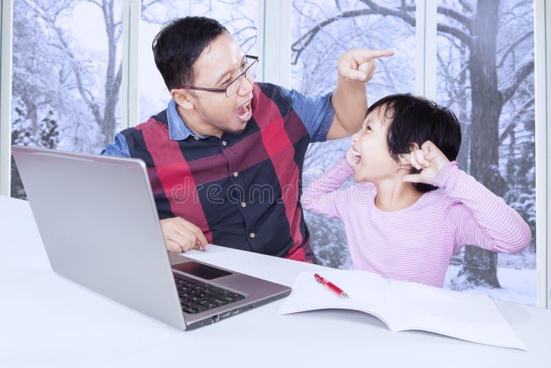 Papa criant sur son enfant pour étudier image libre de droits