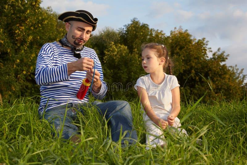 Papa dans le procès de pirate et descendant sur l'herbe image libre de droits
