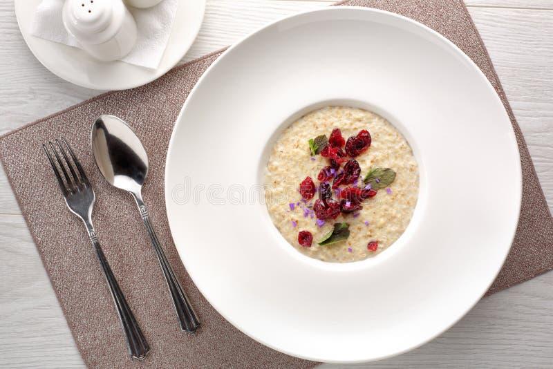 Papa de aveia da farinha de aveia com frutos secados no fundo de madeira branco, café da manhã foto de stock royalty free