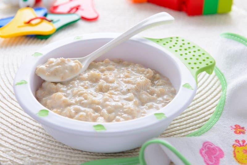 Papa de aveia da farinha de aveia para a nutrição das crianças na toalha de mesa branca com babador foto de stock