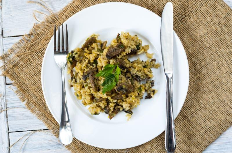 Papa de aveia do arroz com cogumelos Dispositivos brancos da placa e de cozinha fotografia de stock royalty free