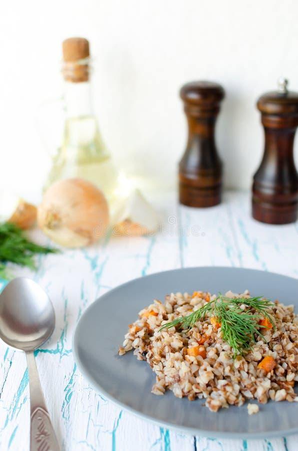 Papa de aveia do trigo mourisco com cenouras e salsa na placa azul No fundo de cebolas douradas, moinhos verdes da salsa e do sal fotografia de stock