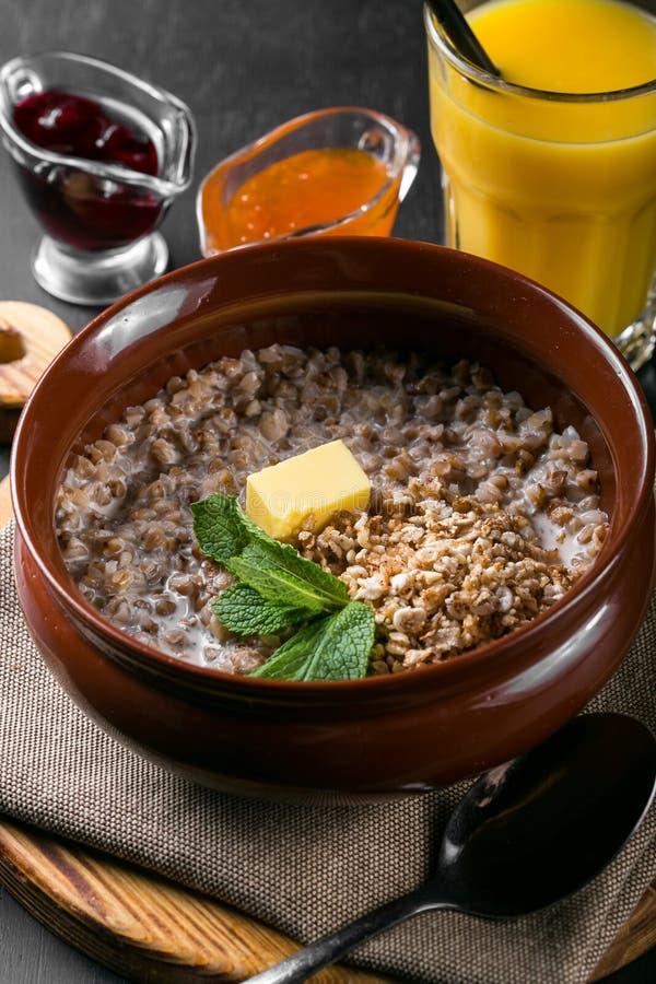 Papa de aveia do trigo mourisco com leite em uma bacia em uma tabela de madeira Café da manhã do papa de aveia do trigo mourisco imagem de stock