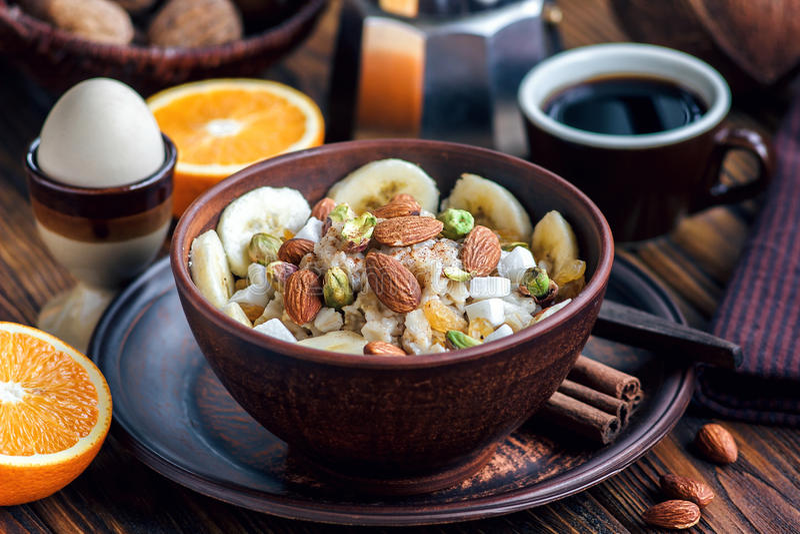Papa de aveia orgânico da farinha de aveia na bacia cerâmica escura com bananas, mel, amêndoas, pistache, microplaquetas do coco, imagens de stock