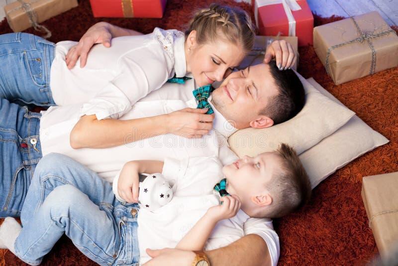 Papa de maman et jeune fils aux cadeaux de nouvelle année de Noël photographie stock libre de droits