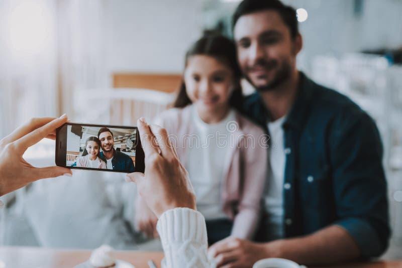 Papa de photographies de mère avec la fille sur le téléphone portable photo stock