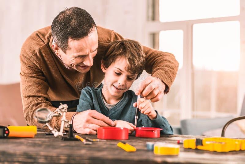 Papa de soin s'occupant de l'itinéraire de son fils au succès photographie stock libre de droits