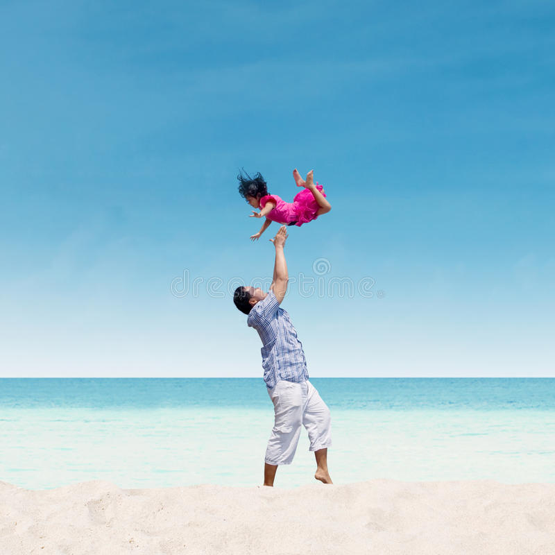 Papa die dochter in lucht werpen bij strand royalty-vrije stock foto
