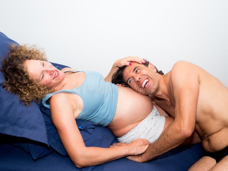 Papa die gelukkig de buik die van haar zwangere vrouw zijn Ne verwachten luisteren royalty-vrije stock foto