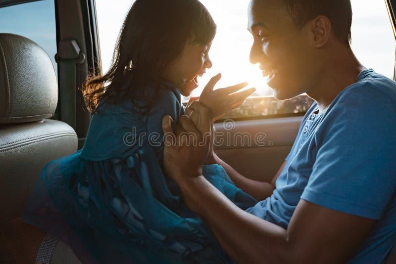 Papa die haar meisje in de auto kietelen stock afbeelding