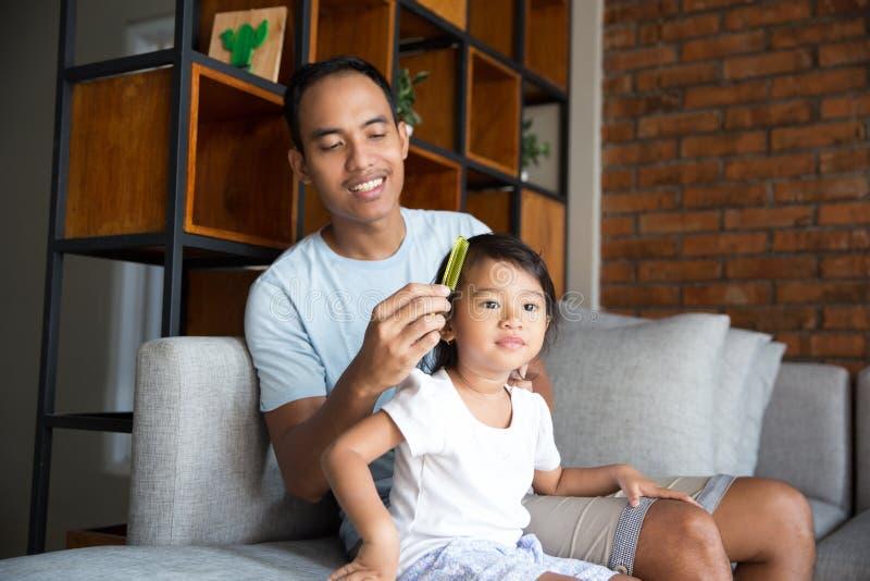 Papa die het haar van het babymeisje kammen stock fotografie