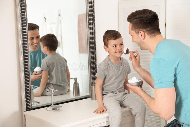 Papa die het scheren schuim op het gezicht van de zoon toepassen royalty-vrije stock afbeelding