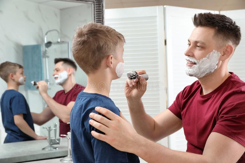 Papa die het scheren schuim op het gezicht van de zoon toepassen bij spiegel stock foto