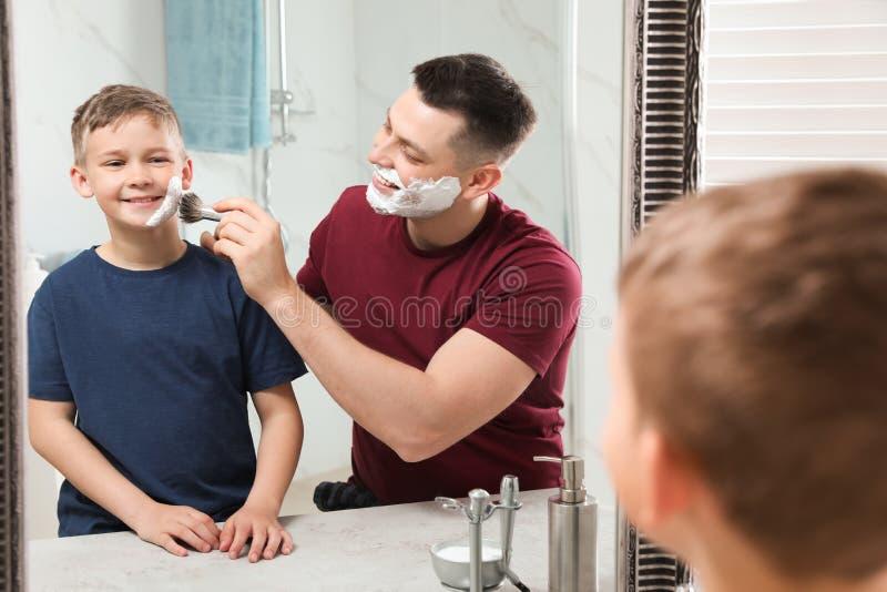 Papa die het scheren schuim op het gezicht van de zoon toepassen bij spiegel royalty-vrije stock foto