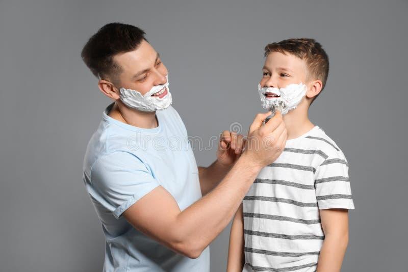 Papa die het scheren schuim op het gezicht van de zoon toepassen stock foto's