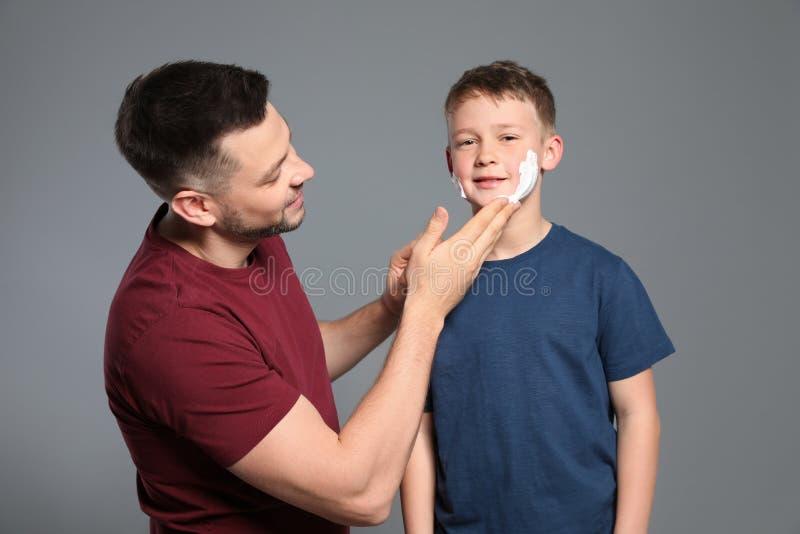 Papa die het scheren schuim op het gezicht van de zoon toepassen stock afbeeldingen