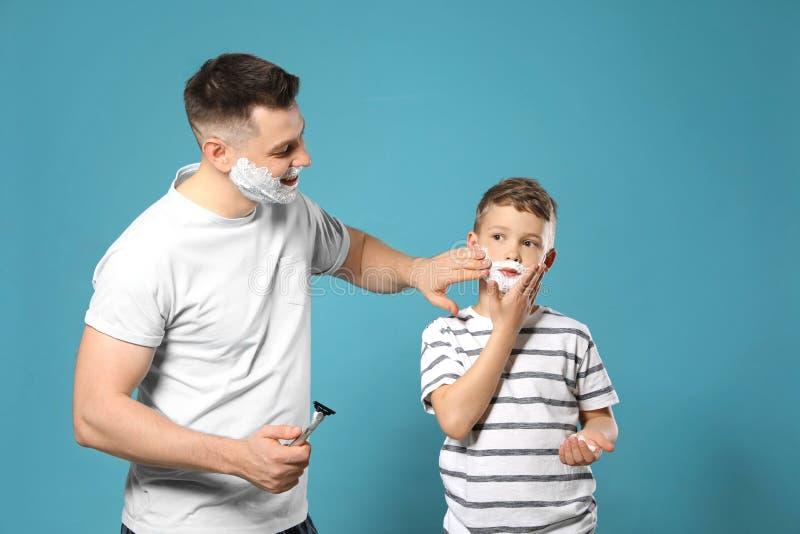 Papa die het scheren schuim op het gezicht van de zoon toepassen stock afbeelding