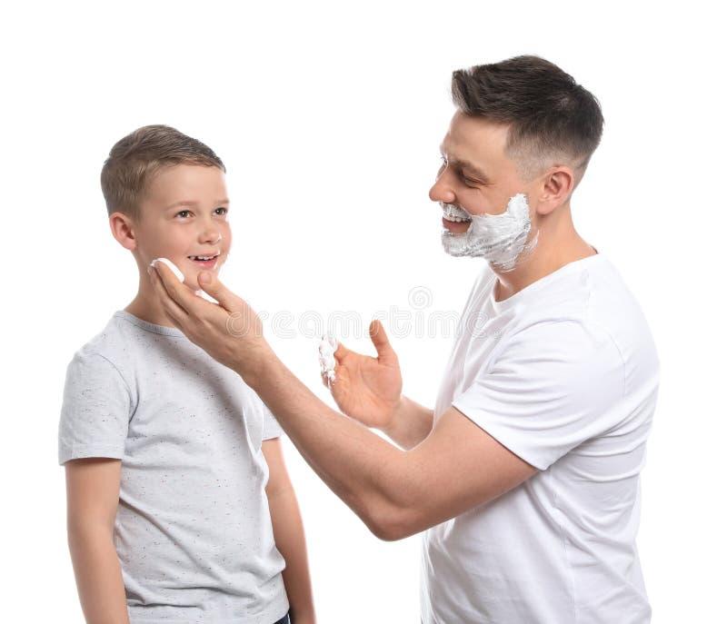 Papa die het scheren schuim op het witte gezicht van de zoon toepassen, stock afbeelding