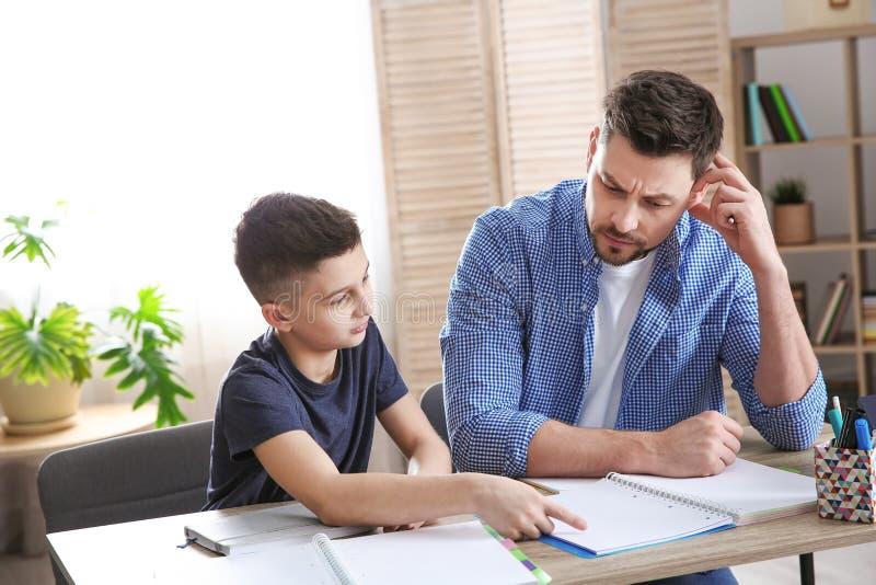 Papa die zijn zoon met thuiswerk helpen royalty-vrije stock afbeeldingen