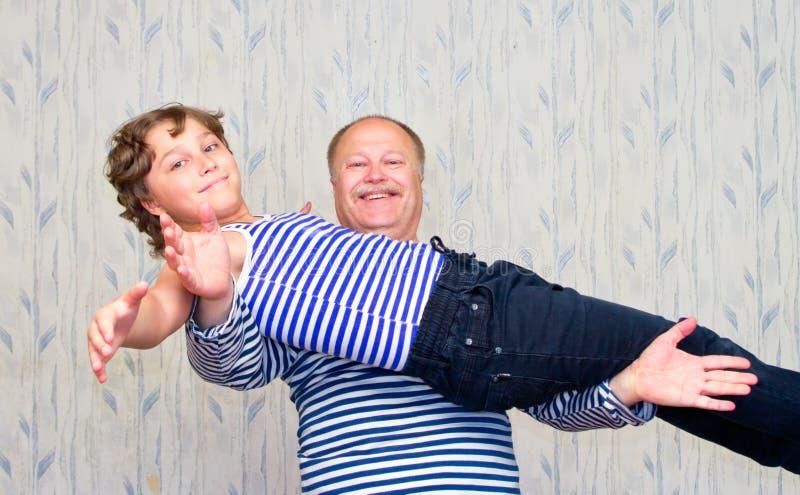 Papa die zijn zoon op zijn uitgestrekte handen houden