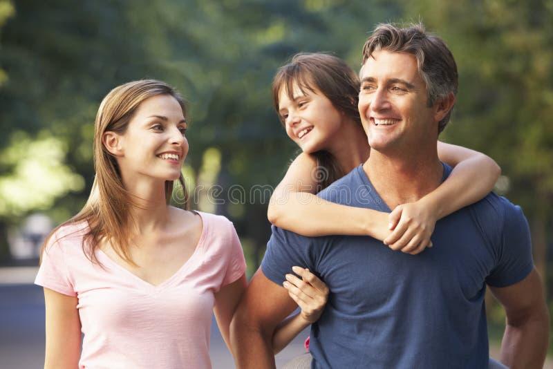 Papa donnant le ferroutage de fille sur la promenade de famille par le parc d'été image stock
