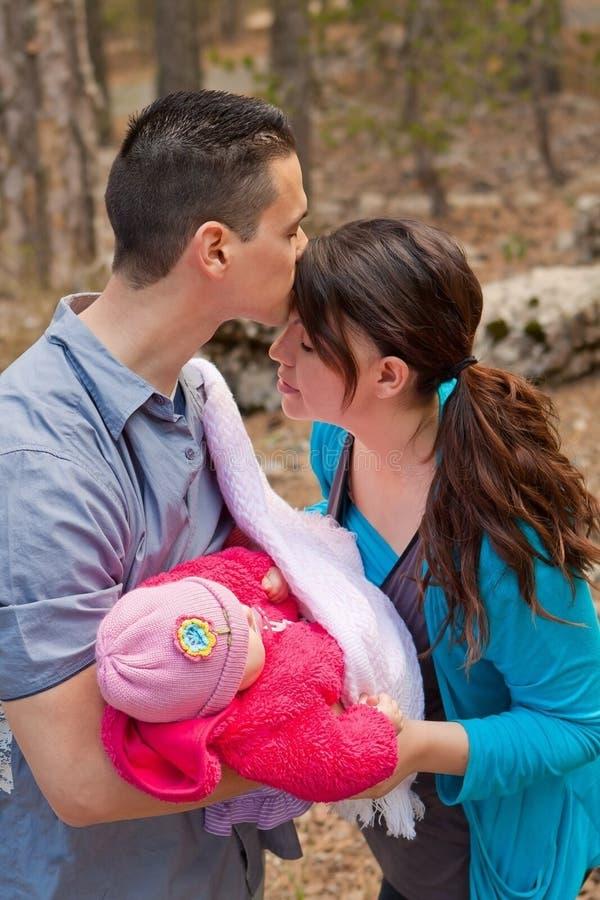 Papa embrassant le front de la maman et tenant le bébé image libre de droits