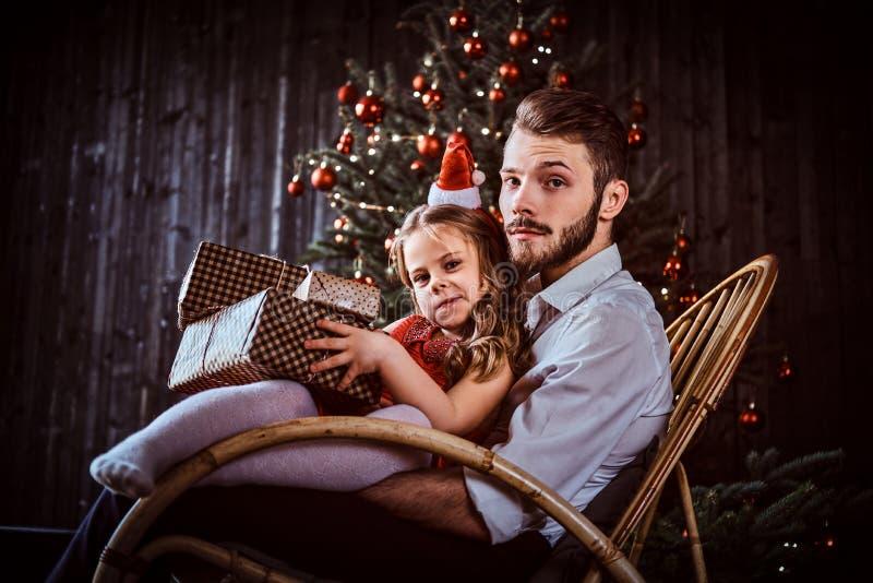 Papa en dochter de dozen van de holdingsgift terwijl thuis het zitten samen op een schommelstoel dichtbij een Kerstboom royalty-vrije stock afbeeldingen