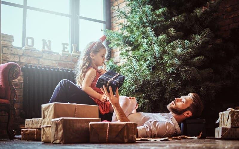 Papa en dochter die die op de vloer liggen, door giften dichtbij de Kerstboom wordt omringd royalty-vrije stock foto
