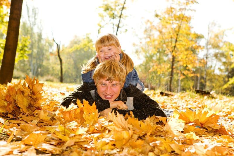 Papa en dochter op de herfstbladeren stock foto's