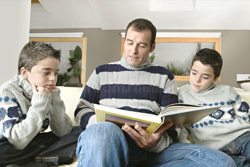 Papa en jonge geitjes die boek lezen stock foto