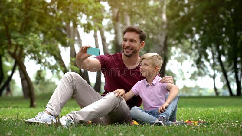 Papa en jongen die selfie op smartphone nemen, die in park bij weekend, vrije tijd rusten stock foto