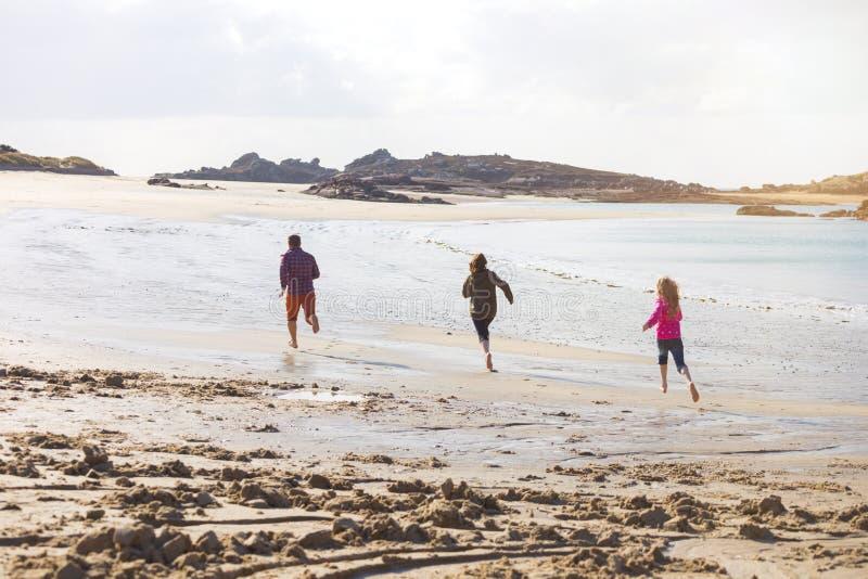 Papa en twee dochters die langs het strand lopen stock afbeeldingen