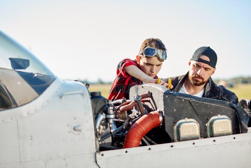 Papa en weinig zoon die samen de reparatiewerken doen bij privé propellervliegtuig royalty-vrije stock fotografie