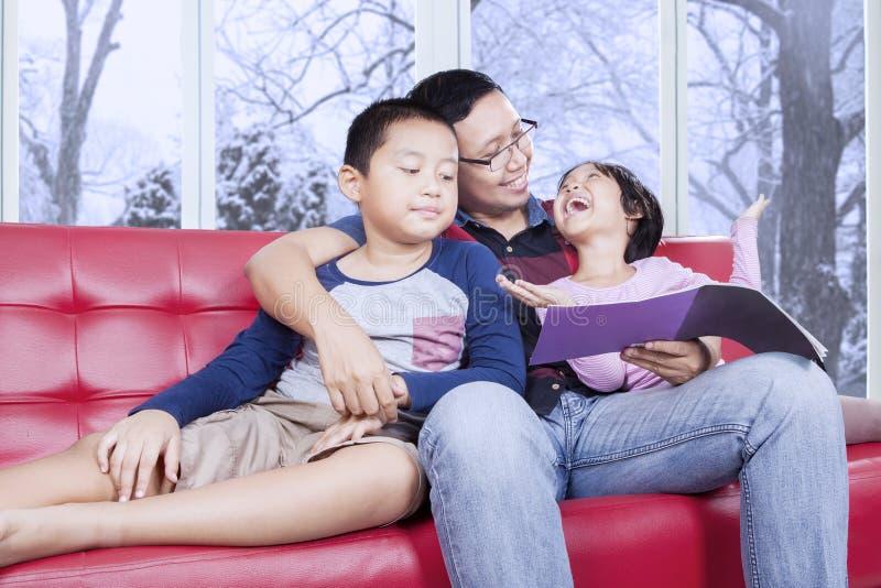 Papa en zijn jonge geitjes die boek op bank lezen royalty-vrije stock fotografie