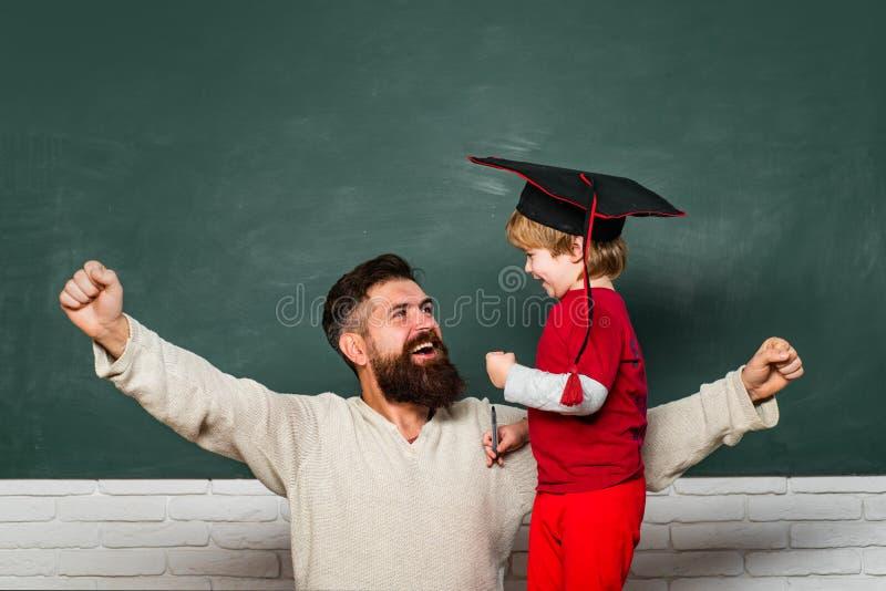 Papa en zijn kleine zoon Papa en zoon samen Terug naar school en onderwijsconcept Het ja goede werk Kind het tonen royalty-vrije stock foto's
