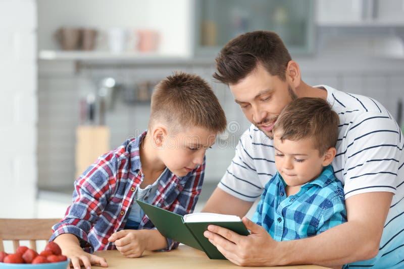 Papa en zijn zonen die interessant boek lezen stock afbeeldingen