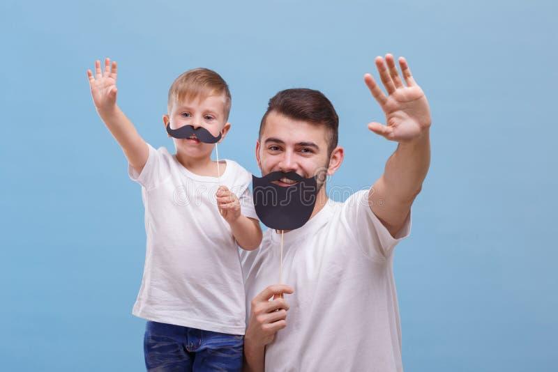 Papa en zijn zoon die hello op een blauwe achtergrond golven stock afbeeldingen