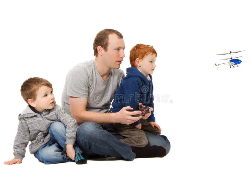 Papa en zonen die het spel van de jonge geitjeshelikopter spelen stock afbeeldingen
