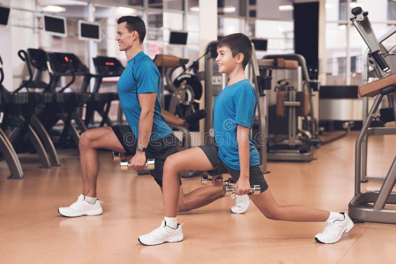 Papa en zoon in dezelfde kleren in gymnastiek De vader en de zoon leiden een gezonde levensstijl royalty-vrije stock foto
