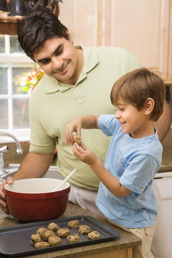 Papa en zoon die koekjes maken. stock fotografie
