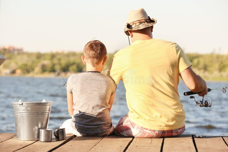 Papa en zoon die van pijler vissen stock foto's