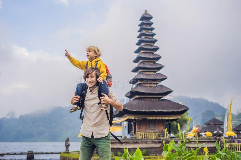 Papa en zoon op de achtergrond van Pura Ulun Danu Bratan, Bali Hindoese die tempel door bloemen op Bratan-meer, Bali wordt omring royalty-vrije stock afbeelding
