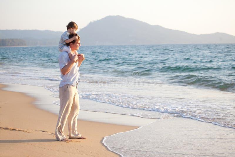 Papa en zoon op het strand stock afbeelding