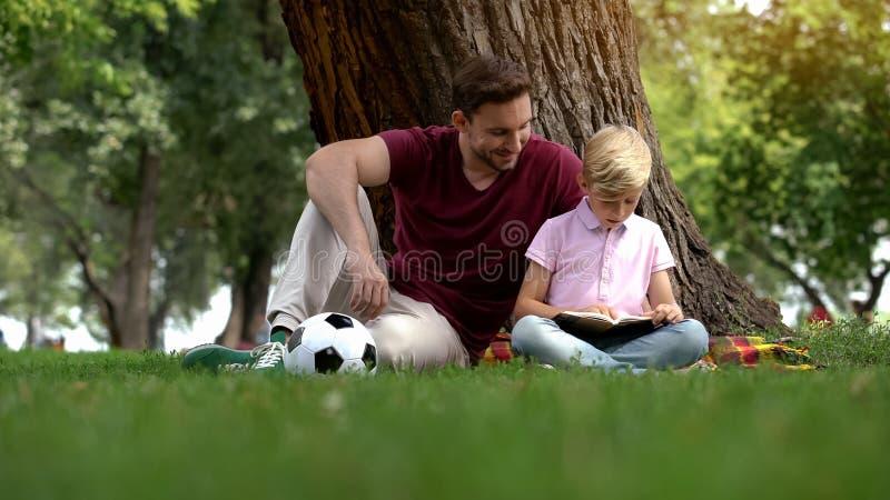 Papa en zoons de lezing boekt, zitting in park onder boom, hobby, samenhorigheid royalty-vrije stock afbeelding