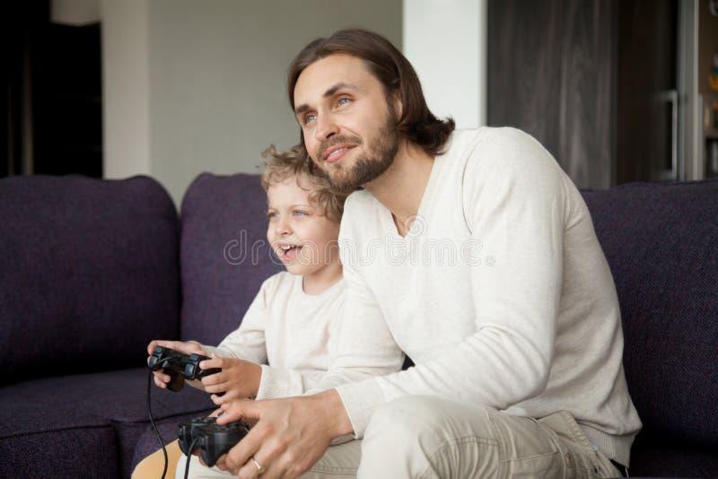 Papa en zoonsholdingsbedieningshendels die spelend videospelletje togeth genieten van stock afbeelding