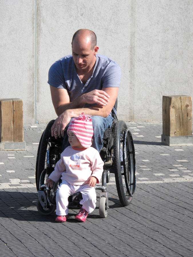 Papa et descendant de fauteuil roulant images stock