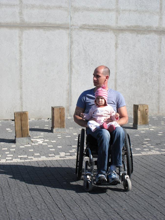 Papa et descendant de fauteuil roulant photo stock